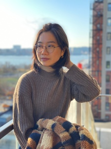 This is an image of Shuyu Fang. Shuyu is looking to the left of the frame and standing on a balcony, holding a warm coat. There is water and skyline behind her that is slightly blurred.